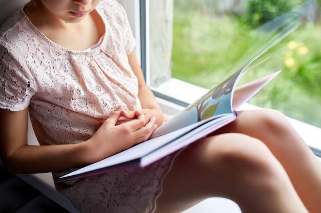 Милая книга чтения маленькой девочки дома, на подоконнике