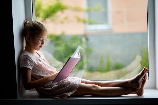 家で本を読んでかわいい女の子