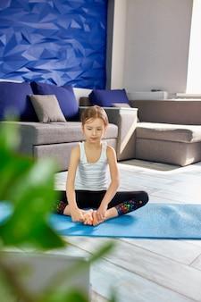 Маленькая девочка практикующих йогу, растяжения, фитнес видео на ноутбуке.