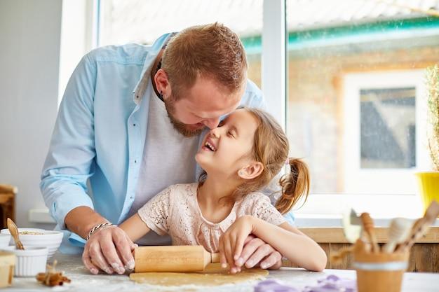 父が彼の小さな娘にクッキーのために生地を転がす方法を示す