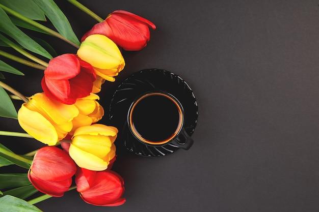 赤と黄色のチューリップの花束と黒のコーヒーカップ。