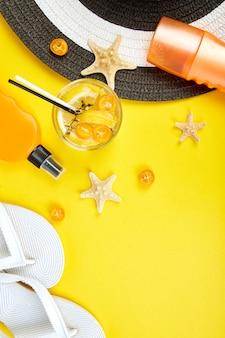 Аксессуары для путешествий или отдыха и газировка на желтом