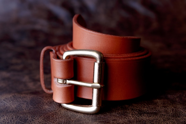 Светло-коричневый ремень с бронзовой пряжкой на черном б