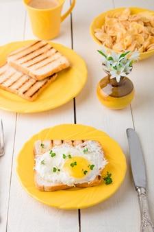 白い木製の背景に花と花瓶に近い黄色のプレートに卵とトーストします。