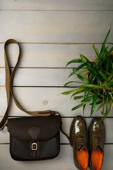 緑の漆塗りのオックスフォードシューズと植木鉢の近くの木製の背景にクロスボディバッグ。
