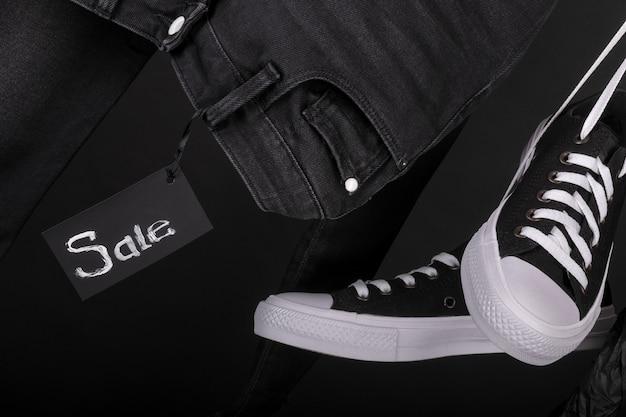 Продажа знак висит черно-белые кроссовки возле джинсы на черном фоне. пятничная распродажа.