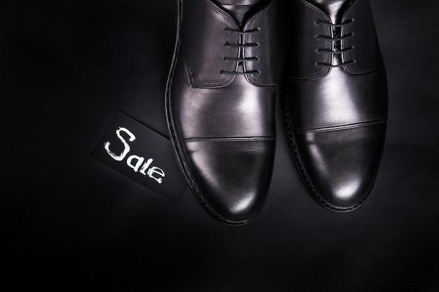 Черные оксфордские туфли на черном фоне. вид сверху. копировать пространство