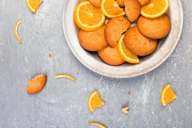 クッキーと灰色の背景上の金属板にオレンジの柑橘系の果物。平置き