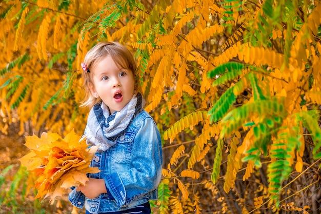 Маленькая девочка с желтыми осенними золотыми листьями. детская игра на открытом воздухе в парке. вот это да.