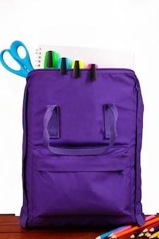 Раскройте фиолетовый рюкзак с школьными принадлежностями на деревянном столе. обратно в школу.