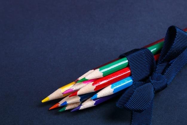 黒の木製の背景にスニーカーの近くの青いリボンに包まれた色鉛筆のセット。学校に戻る。