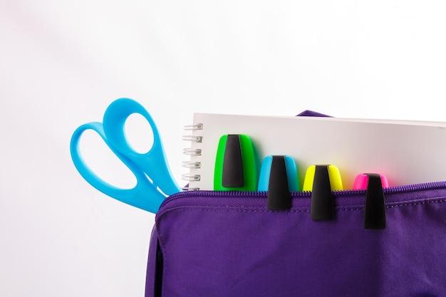 学用品の入った紫色のバックパックを開けます。学校に戻る。