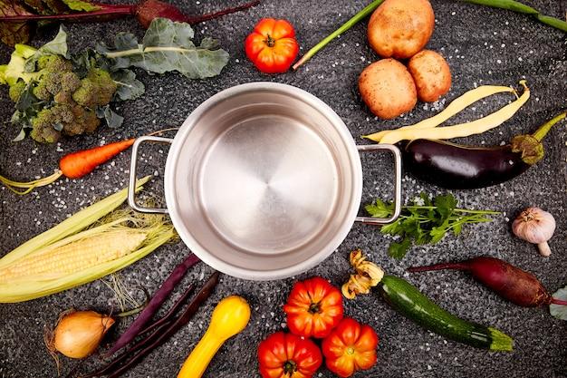 空の調理鍋の周りのさまざまな有機野菜成分