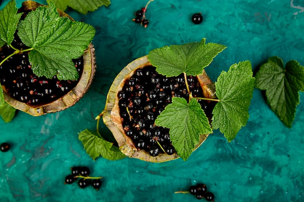 ブラックカラントの果実、葉、緑のボウルに黒スグリ。