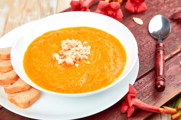 白いプレートにカボチャのスープのクリーム。感謝祭。