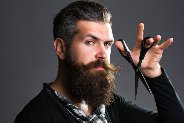 長いひげ口ひげを持つ若いハンサムなひげを生やした男