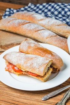 Открытый сэндвич с прошутто, моцарелла и помидоры на кухонном столе, мелкой фокус