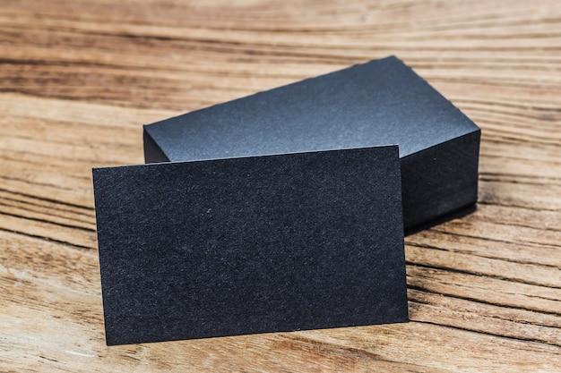 木製の背景に空の黒い名刺のスタック