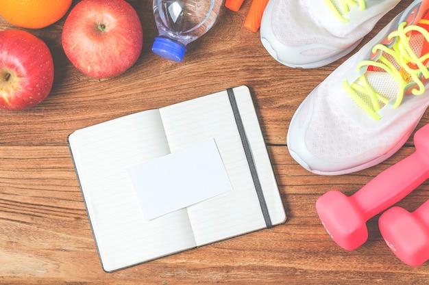 Фитнес, здоровый и активный образ жизни концепция, бутылка воды, гантели, спортивная обувь, смартфон с наушниками и яблоками на фоне дерева. скопировать место для текста. вид сверху