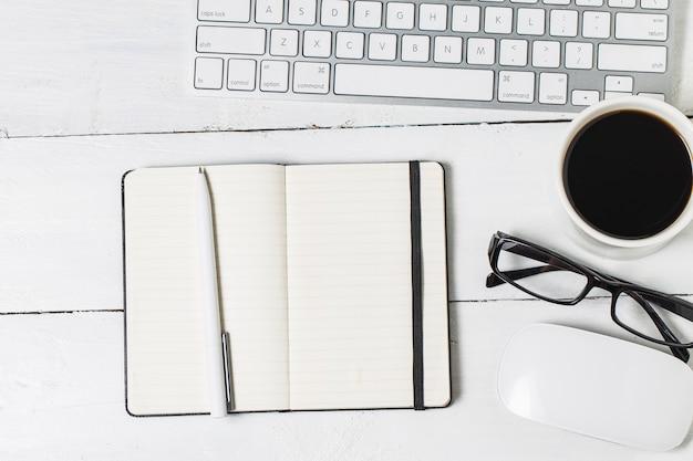 デザイナーのための空白の書類テンプレート。ヴィンテージ木製の背景に反応的なデザインモックアップ。紙、レターヘッド、コーヒーカップ、スマートフォン、鉛筆、木製のテーブルの背景にヘッドフォン。上面図。