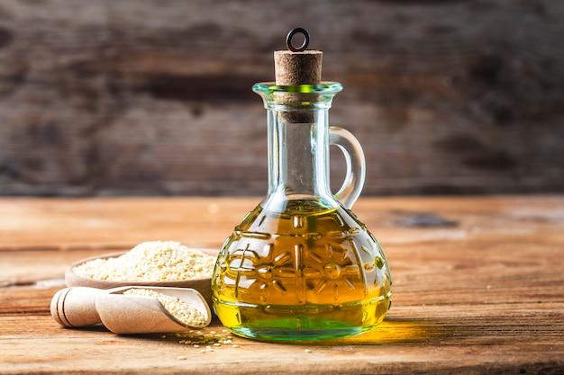 Семена кунжута и бутылка с маслом на старом деревянном столе? кунжутное масло в стеклянном кувшине.