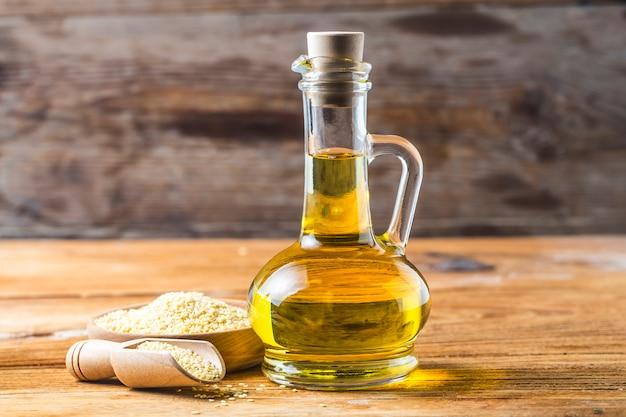 ゴマ種子、古い木製のテーブルに油を入れたボトル、ガラスジャグのゴマ油。