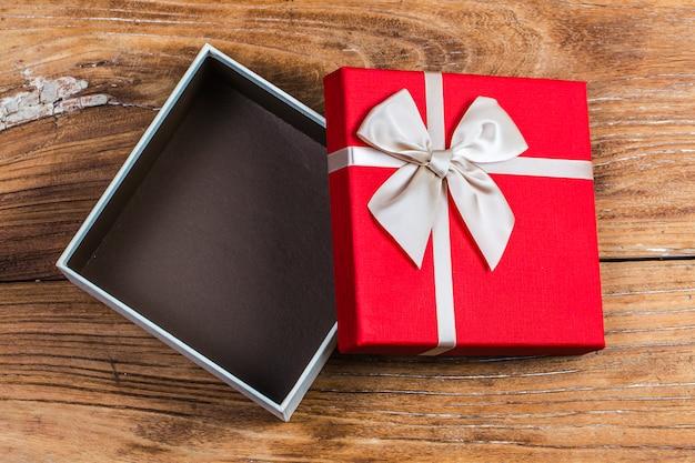 ギフトボックスは赤いリボンに小さな赤いハートが印刷されています。古い木製の背景に。