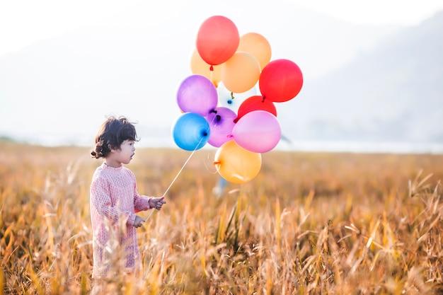 麦畑に風船で遊んで小さな女の子