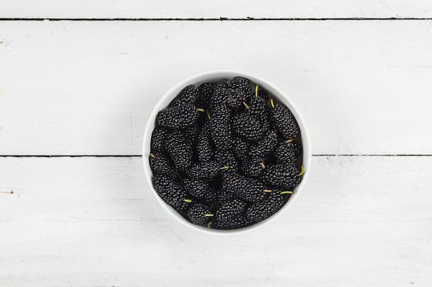 Плоды шелковицы в белой миске на деревянный стол