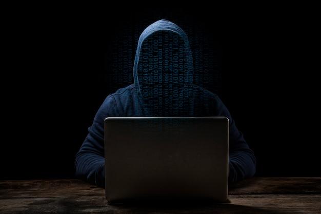 Анонимный компьютерный хакер над абстрактной цифровой предпосылкой. затененное темное лицо в маске и капюшоне.