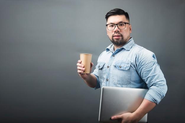 コンピューターとコーヒーを保持している中年の男性