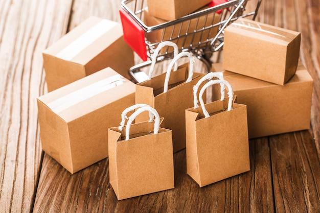 Покупки онлайн на дому концепции. картонные коробки в корзине для покупок на клавиатуре ноутбука. интернет-магазины - это форма электронной торговли, которая позволяет потребителям напрямую покупать товары у продавца через интернет.