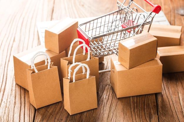 ホームコンセプトでのオンラインショッピング。ノートパソコンのキーボード上のショッピングカート内のカートン。オンラインショッピングは、消費者がインターネット経由で売り手から商品を直接購入できる電子商取引の一種です。