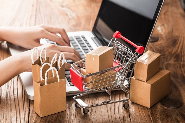 Покупки онлайн дома. картонные коробки в корзине на клавиатуре ноутбука