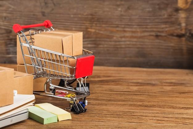 ホームコンセプトでオンラインショッピング。ノートパソコンのキーボードのショッピングカート内のカートン