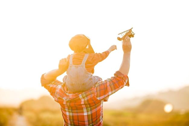 子供と日没時の自然の中でおもちゃの飛行機を持つ彼女の父