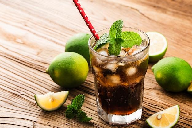 木製の表面に茶色のラム酒、コーラ、ミント、レモンを使ったフレッシュなキューバリブレ