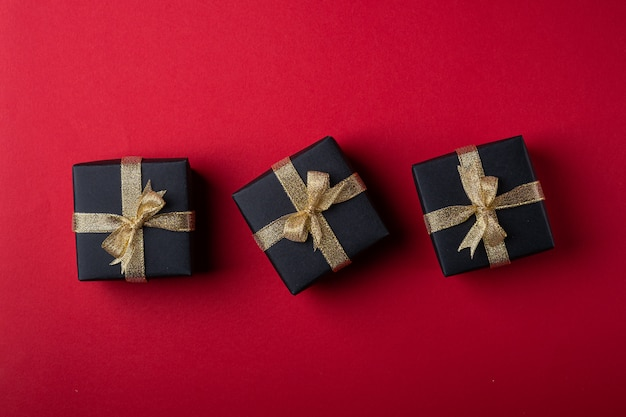 Три черные подарочные коробки с золотыми лентами в линию на красной бумажной стене, вид сверху