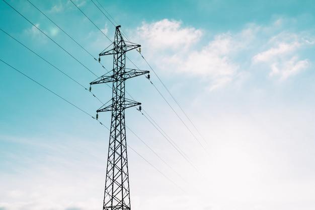 青い雲の上の電力線タワー
