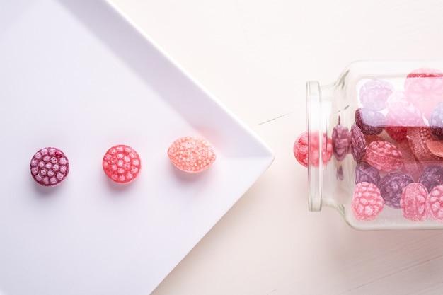 Три леденцы на белой тарелке с конфетами в виде сочных ягод в стеклянной банке на белом
