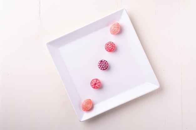 Пять конфет конфет в виде сочных ягод на белой тарелке