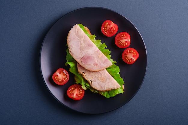 七面鳥のハム肉、グリーンサラダ、ブラックプレート、青い最小限のテーブル、トップビューで新鮮なチェリートマトのスライスのサンドイッチ