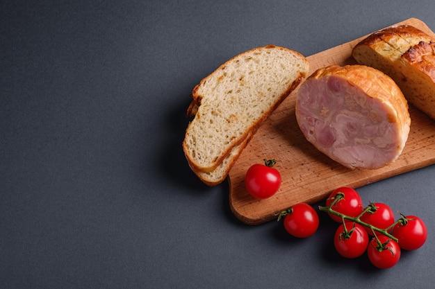 トルコのハム肉、新鮮なチェリートマトの枝、パンは木製のまな板、灰色の最小限のテーブルでパンをスライス