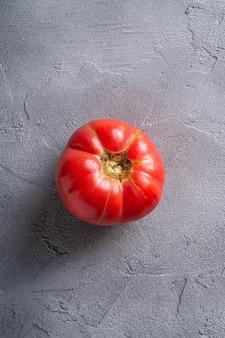Один розовый помидор овощной реликвии, свежие красные спелые помидоры, веганская еда, камень бетонный фон, вид сверху