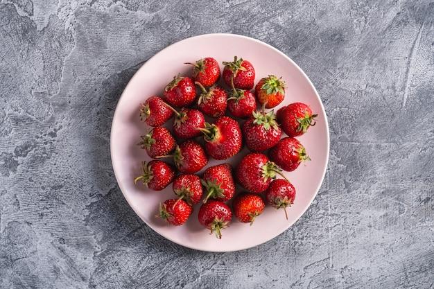 ピンクプレート、灰色の石の背景、上面に夏のビタミン果実で新鮮な熟したイチゴ果実