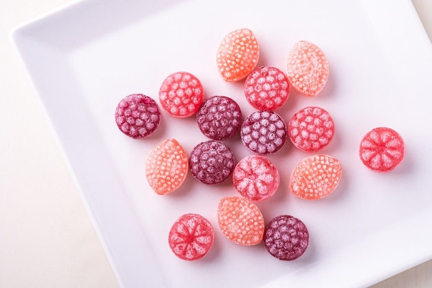 白い背景の分離、トップビューで白い皿にジューシーな果実の形のキャンディー杖お菓子