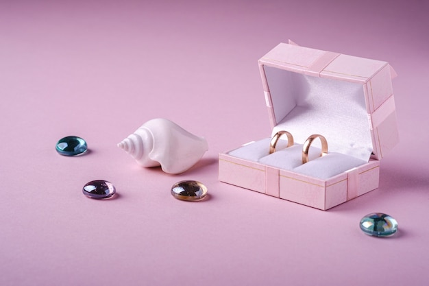 柔らかいピンクの背景、アングルビュー、コピースペースに白い貝殻とガラスのビー玉とピンクのギフトボックスに結婚式の金の指輪