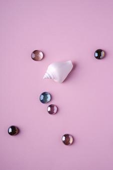 Белая морская ракушка с блестящими стеклянными разноцветными шариками на нежно-розовом фоне, вид сверху