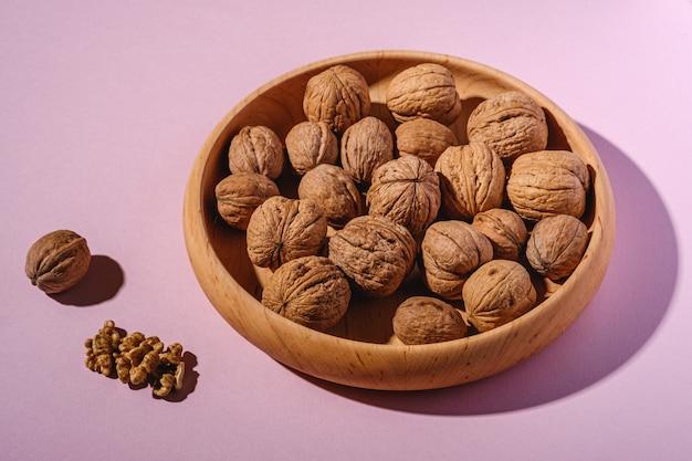 Грецкие орехи кучи пищи в деревянной миске на розовом фоне рядом с очищенными орехами, угол зрения, концепция здорового питания