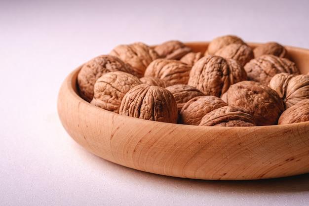 Еда кучи грецких орехов в деревянном шаре на белой предпосылке, взгляде угла, концепции здоровой еды